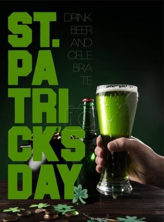 vue partielle de l'homme avec le verre de bière et st inscription journée patricks