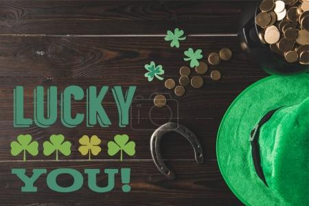 flat lay with horseshoe, hat and pot of gold on wooden tabletop with lucky you lettering