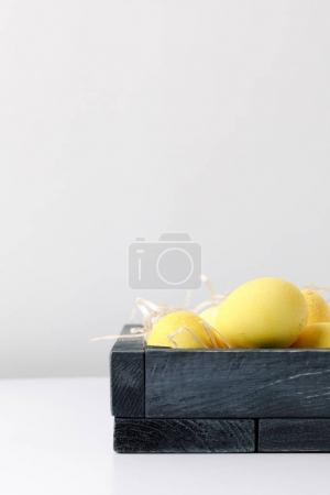 yellow painted easter eggs in wooden box on white table
