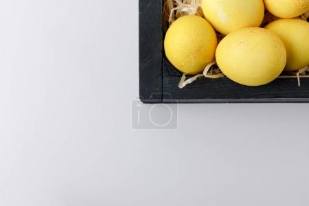 top view of yellow painted easter eggs in wooden box isolated on white
