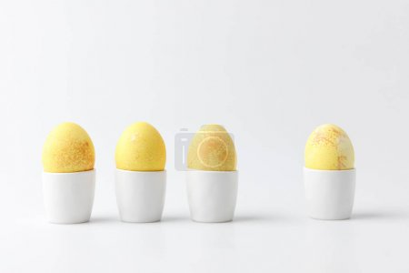 four yellow painted easter eggs in egg stands on white