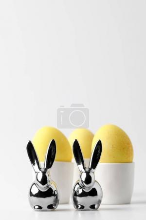 Photo for Yellow painted easter eggs in egg stands and statuettes of rabbits on white - Royalty Free Image
