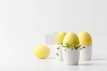 yellow painted easter eggs in egg stands on white