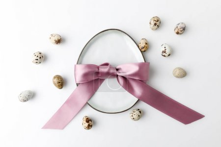 top view of plate in shape of egg with quail eggs on white, easter concept