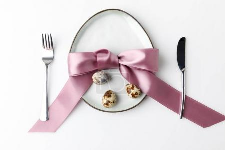 top view of plate in shape of egg with fork and knife with quail eggs isolated on white, easter concept