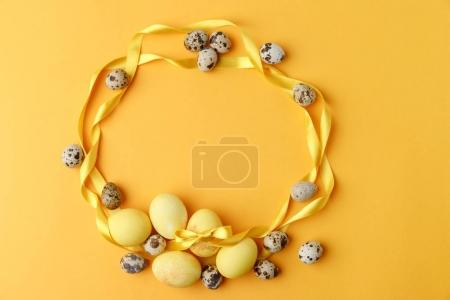 Photo for Top view of yellow painted easter eggs and quail eggs on yellow - Royalty Free Image