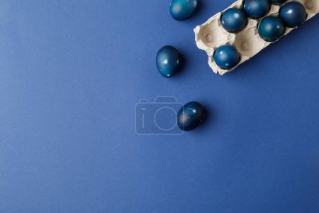 top view of blue painted easter eggs and egg tray on blue surface