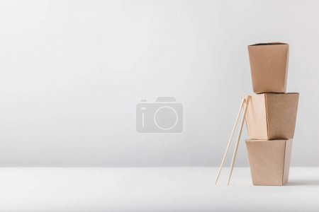 three noodles boxes with chopsticks on table