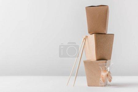 Foto de Cajas de fideos con palillos y galleta de la fortuna China sobre mesa - Imagen libre de derechos