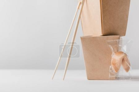 noodles boxes with chopsticks and chinese fortune cookie on table