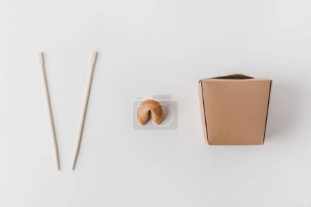 top view of noodles box with chopsticks and chinese fortune cookie