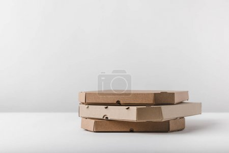 Photo for Three pizza boxes on white tabletop - Royalty Free Image