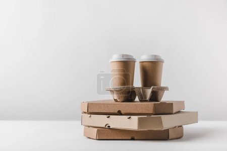 disposable coffee cups on pizza boxes on table