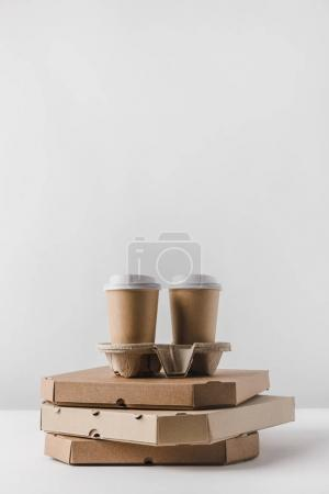 coffee in paper cups on pizza boxes on table