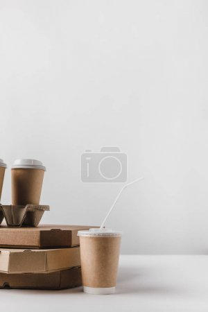 pizza boxes and coffee in paper cups on table