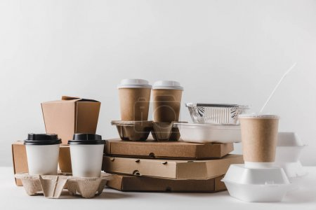 pizza boxes and coffee in paper cups with wok boxes on tabletop