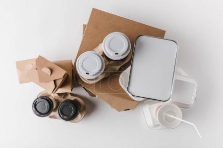 Photo pour Vue du dessus des boîtes à pizza et café dans des tasses en papier avec des boîtes de wok sur la table - image libre de droit