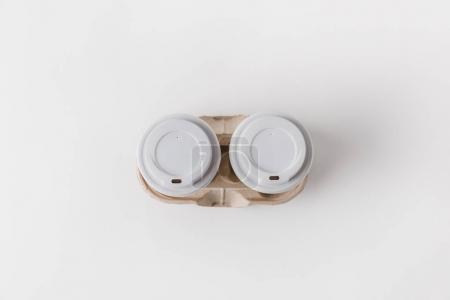 Photo pour Vue du dessus du café dans des tasses en papier dans un plateau en carton sur la table - image libre de droit