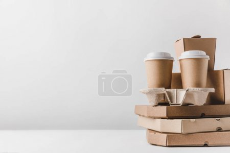 pizza boxes and disposable coffee cups with noodles boxes on tabletop