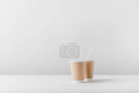 two disposable coffee cups on white surface