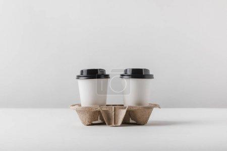 Photo pour Deux café dans des tasses en papier dans un plateau en carton sur la table - image libre de droit