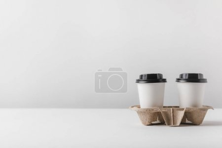 two coffee in paper cups in cardboard tray on table