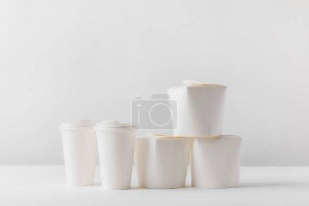 Photo pour Boîtes à emporter et café dans des tasses en papier sur table blanche - image libre de droit