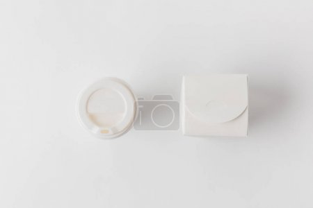 top view of disposable coffee cup and noodles box on white surface