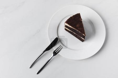 Photo for Chocolate cake on plate with fork and knife on white surface - Royalty Free Image