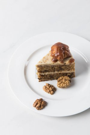 Cake on white plate surrounding by walnuts on table