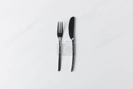 Fork and knife placed on white surface, table appointments conception