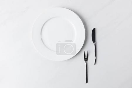Photo pour Vue du dessus de la plaque avec fourchette et couteau, conception des rendez-vous de table - image libre de droit
