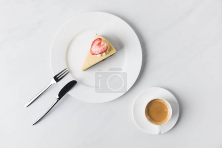 Photo for Cheesecake with strawberry on top and cup of coffee on table - Royalty Free Image