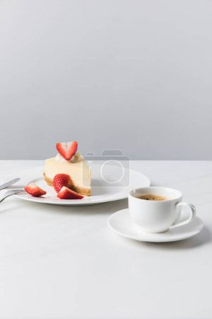 Coffee cup and cutlery near plate with strawberry cheesecake