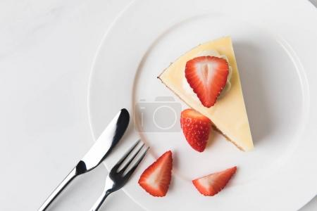 Photo for Plate with cheesecake surrounding by sliced strawberries - Royalty Free Image