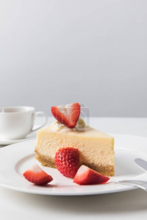 Photo for Closeup view of coffee cup and plate with strawberry cheesecake - Royalty Free Image