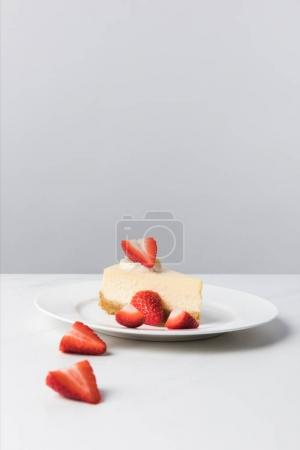 Photo for Closeup view of plate with cheesecake surrounding by sliced strawberries on table - Royalty Free Image