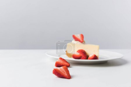 Photo for Plate with cheesecake surrounding by fresh sliced strawberries - Royalty Free Image
