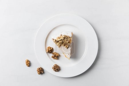 Photo for Plate with cake surrounding by walnuts placed on white surface - Royalty Free Image