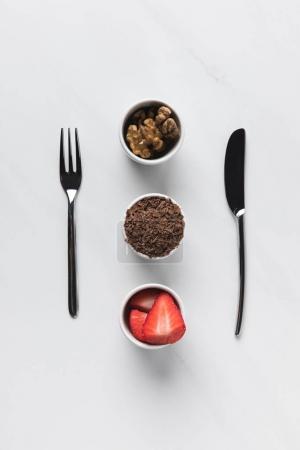 Photo pour Bol aux noix, chocolat râpé et fraises entre fourchette et couteau, conception des tables - image libre de droit