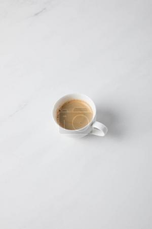 Top view of coffee cup placed on white surface