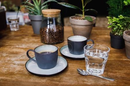 Cups of coffee and glass of water on table in cozy coffee shop