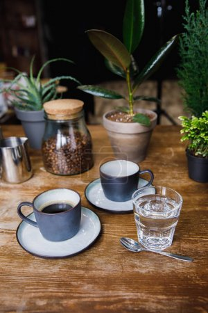 Cups of coffee and glass of water on cafe table