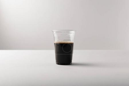 Plastic cup with black coffee on white background