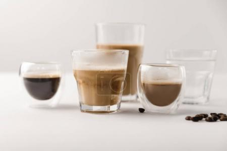 Glasses with assorted coffee drinks on white background with coffee beans
