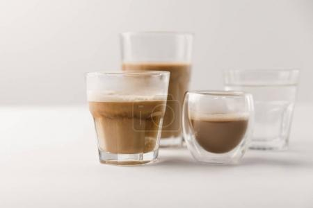 Glasses with coffee and milk on white background