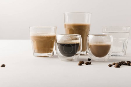 Set of cups with assorted coffee drinks on white background