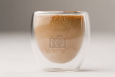 Glass cup filled with coffee with milk on white background