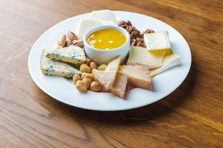 Photo for Close-up view of delicious cheese plate with nuts and honey on wooden tabletop - Royalty Free Image