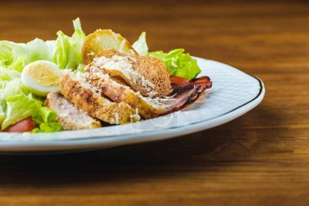 close-up view of delicious caesar salad on wooden table